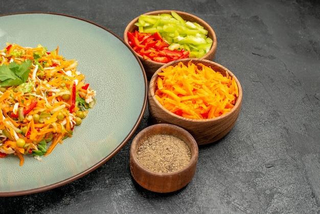 灰色のテーブルの材料と正面図の野菜サラダ健康ダイエット食品サラダ