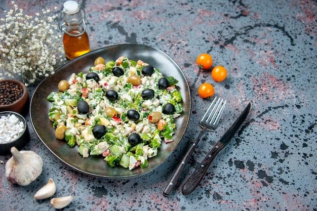 Вид спереди овощной салат с майонезом и оливками внутри тарелки на синей поверхности цвет здоровье диета ужин блюдо фото еда
