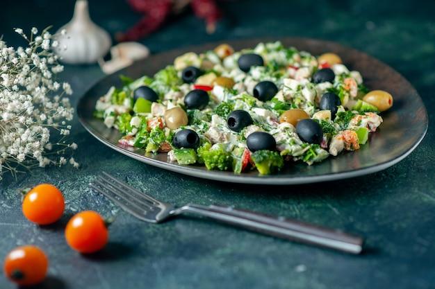 Овощной салат с майонезом и оливками на темно-синей поверхности вид спереди еда праздник здоровье блюдо фото ужин цвета
