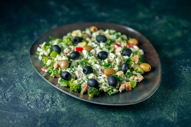 Front view vegetable salad with mayyonaise and olives on dark blue surface meal color holiday health dish photo dinner