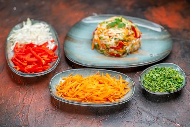 スライスしたニンジンキャベツと暗い背景のピーマンと正面図野菜サラダダイエット食品健康的な生活食事の色