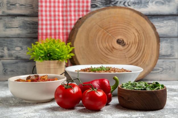 Zuppa di verdure vista frontale con grano saraceno e pomodori su spazio bianco