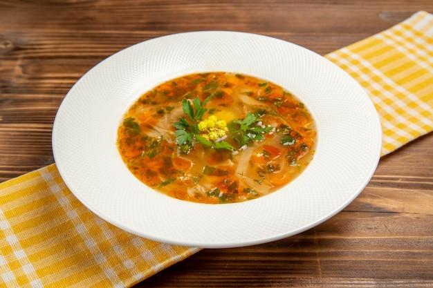 Zuppa di verdure vista frontale con verdure su condimenti vegetali di cibo minestra tavolo in legno marrone