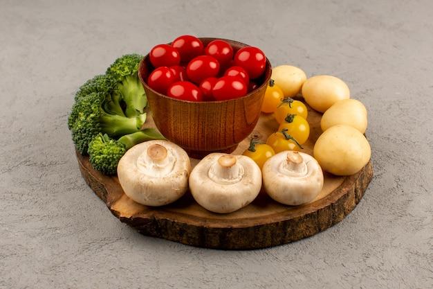 Vista frontale verdure funghi pomodori broccoli e patate sul pavimento grigio
