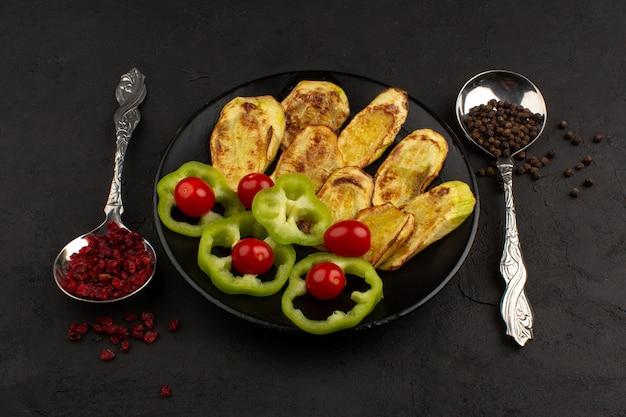 正面の野菜の赤いチェリートマトと暗い床に黒いプレートの中のピーマン