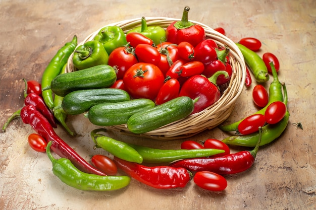 Front view vegetables in a wicker basket surrounded by peppers and cherry tomatoes on amber background