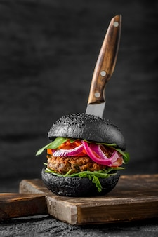 Front view veggie burger with black buns on cutting board with knife