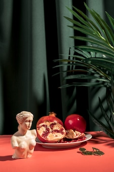 Front view venus bust next to pomegranates
