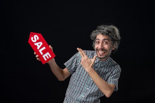Vista frontale di un uomo molto eccitato che tiene in mano il cartello di vendita rosso sul muro scuro