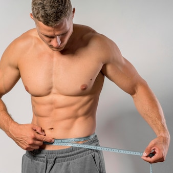 Front view of very fit man holding measuring tape around waist
