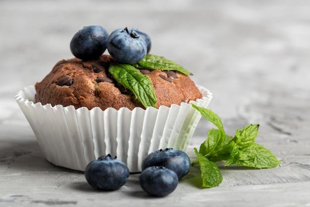 Vista frontale vista gustoso cupcake con mirtilli e menta