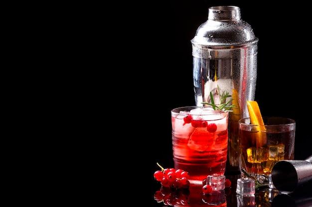 Водка, клюква и виски, вид спереди с апельсином с копией пространства