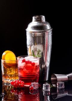Vista frontale vodka mirtillo rosso e whisky con bicchieri arancioni