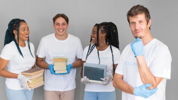 Волонтерская организация, вид спереди, держит книги для пожертвований