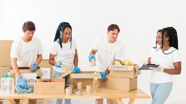 Волонтеры вид спереди заботятся о пожертвованиях