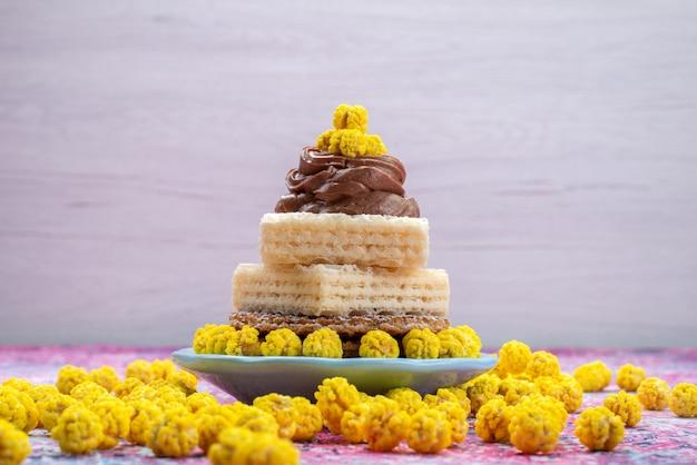 Вафельные коржи со сливками и желтые конфеты, вид спереди