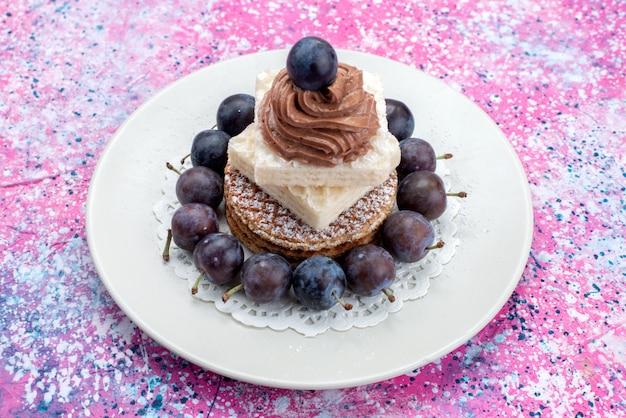 Torte waffle vista frontale con crema e uva all'interno del piatto bianco