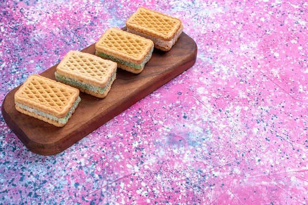 Вафельное печенье вид спереди с фруктовой кремовой начинкой на розовом фоне.