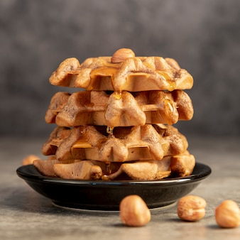 Front view of waffles stacked on plate with honey and hazelnuts