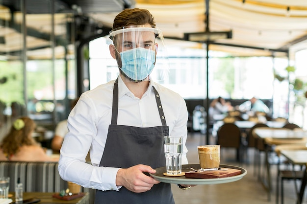 Front view waiter with mask serving