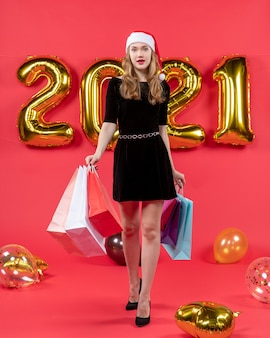 Front view walking young lady in black dress holding shopping bags balloons on red