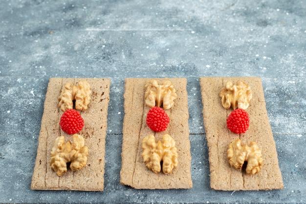 Вид спереди на грецкие орехи и малину, выложенные на чипсах и в ягоде с легкими орехами