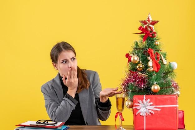 テーブルに座っている正面の放浪の女の子クリスマスツリーとギフトカクテル
