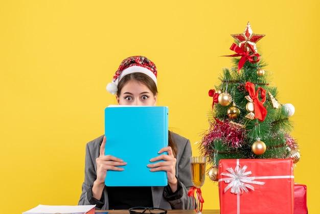 フォルダークリスマスツリーとギフトカクテルで顔を覆うテーブルに座っているクリスマスの帽子をかぶった正面図放浪少女