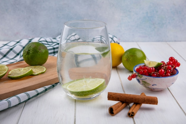 Front view of water in a glass with lime and lemon on a board with cinnamon and red currants on a white surface