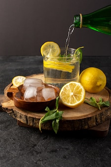 A front view water with lemon fresh cool drink inside glass pouring with green leaves with ice cubes with sliced lemons on the dark