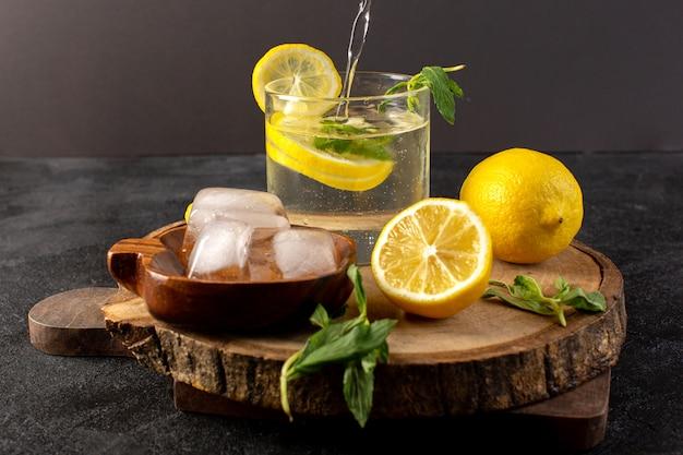 Un'acqua vista frontale con bevanda fresca fresca di limone all'interno di vetro versando con cubetti di ghiaccio con fette di limoni sul buio