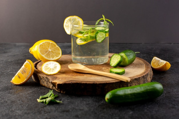 A front view water with lemon fresh cool drink inside glass with green leaves with ice cubes sliced lemons cucumber on the dark