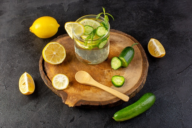 A front view water with lemon fresh cool drink inside glass with green leaves with ice cubes with sliced lemons cucumber on the dark