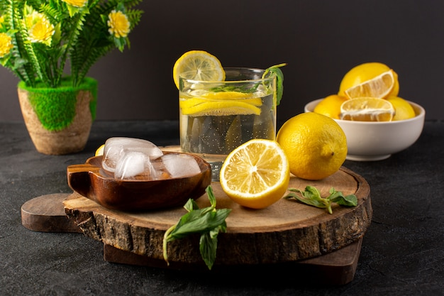 A front view water with lemon fresh cool drink inside glass with green leaves with ice cubes with sliced lemons on the dark