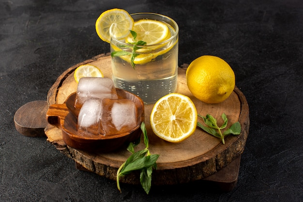 A front view water with lemon fresh cool drink inside glass with ice cubes with sliced lemons on the dark
