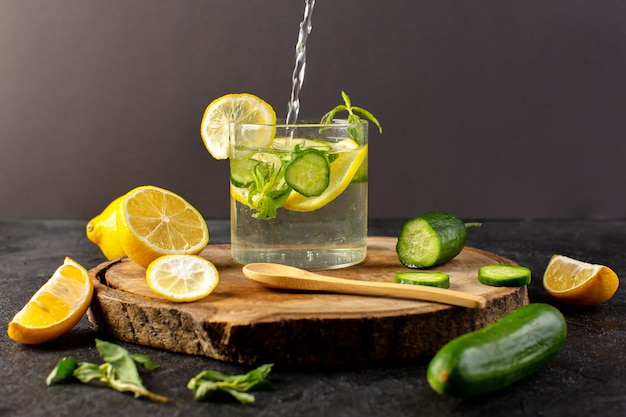 A front view water with lemon fresh cool drink pouring inside glass with green leaves with ice cubes with sliced lemons cucumber on the dark