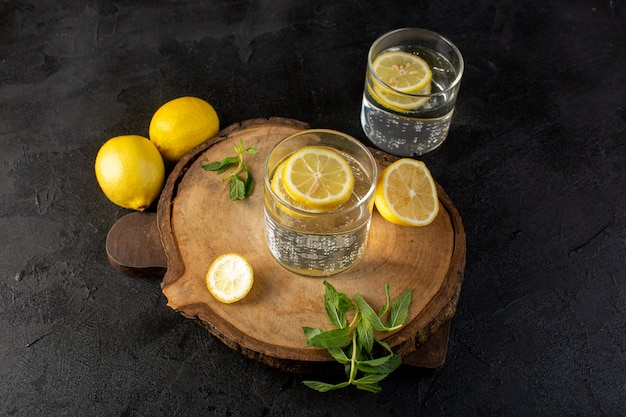 A front view water with lemon fresh cool drink with sliced lemons along with whole lemons and leaves inside transparent glasses on the dark