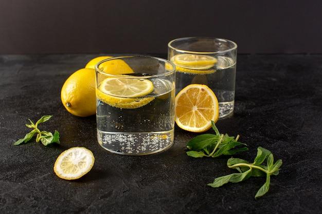 Una vista frontale acqua con limone fresca bevanda fresca con fette di limoni insieme a limoni interi e foglie all'interno di bicchieri trasparenti sul buio