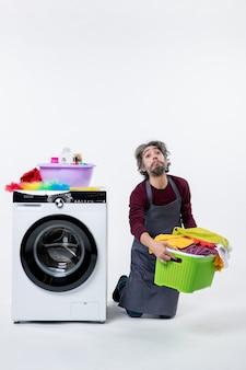 白い壁に洗濯かごを持って膝の上に立っている正面図疲れた家政婦の男