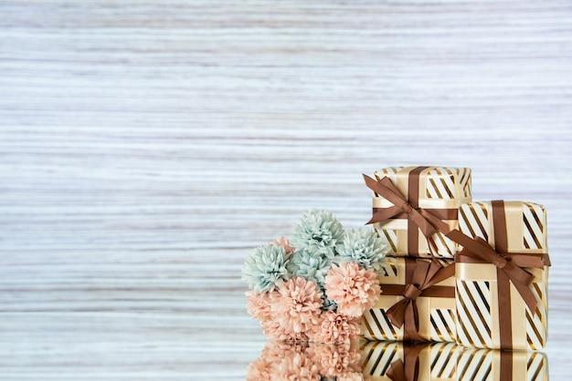 I fiori dei regali di nozze di vista frontale si riflettono sullo specchio su sfondo chiaro con spazio libero