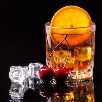 Виски вид спереди с апельсином и вишней
