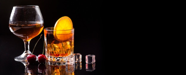 Виски, вид спереди с апельсином и бокалом для коньяка с копией пространства