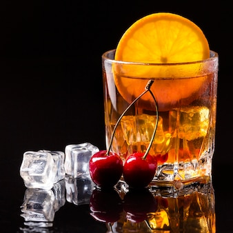 Front view whiskey with orange and cherries