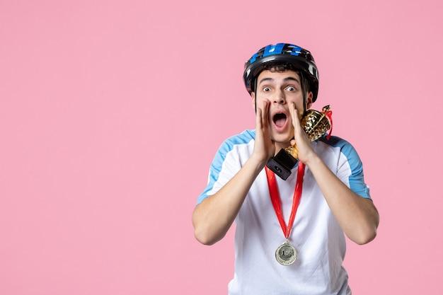 Вид спереди шепчущий мужчина-спортсмен в спортивной одежде держит золотой кубок в шлеме