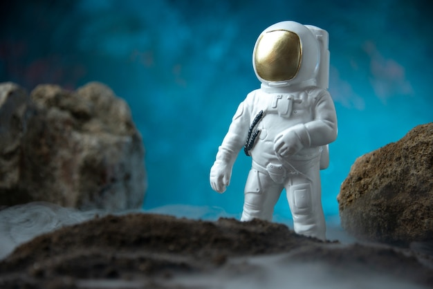 Front view of white astronaut with rocks on moon blue desk death sci fi funeral