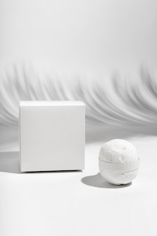 Front view white bath bomb next to box
