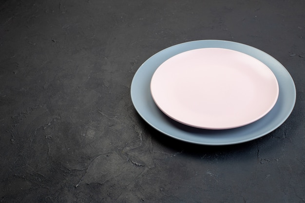 Front view of white and blue ceramic empty plates on black background with free space