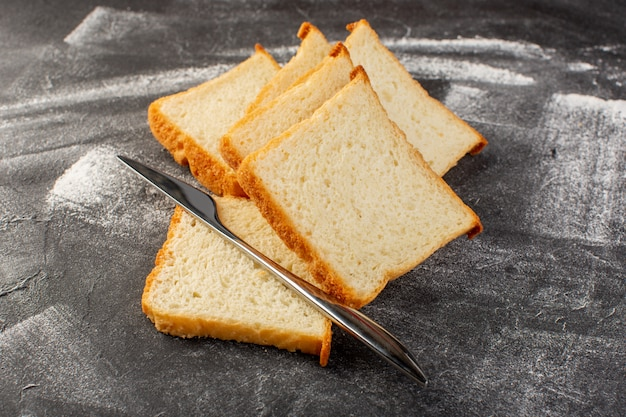 Front view white bread loafs sliced and tasty isolated with knife on grey