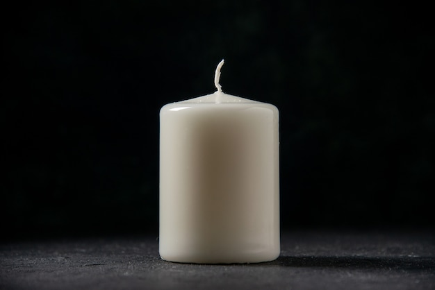 Front view of white candle on black