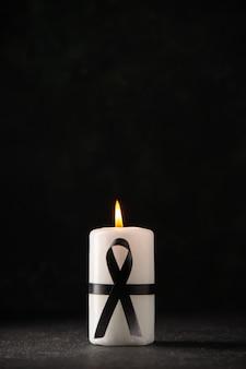 Vista frontale della candela bianca su oscurità